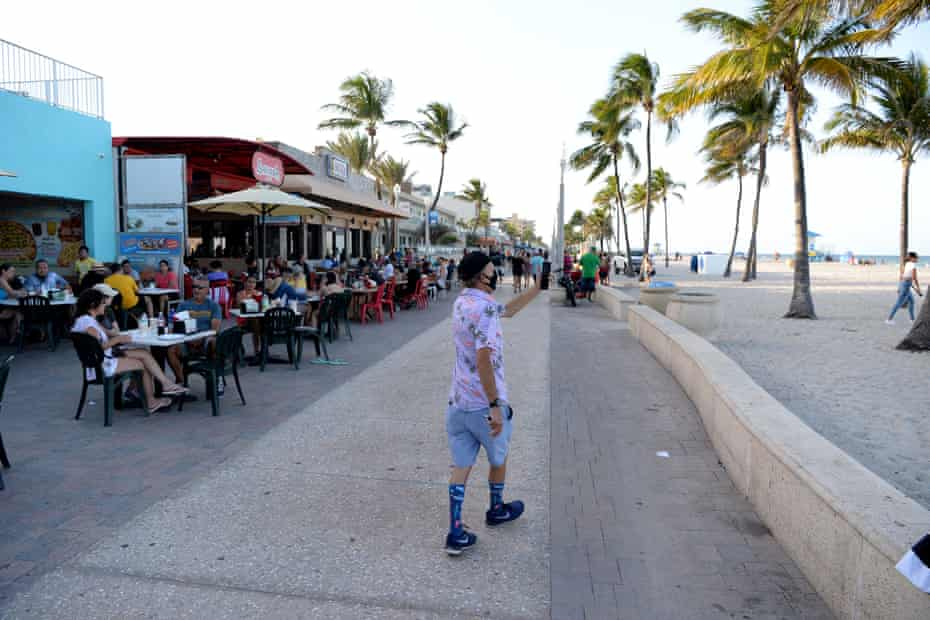 People walk on the Hollywood Beach Boardwalk as Florida reports another surge in coronavirus cases, on 26 June.