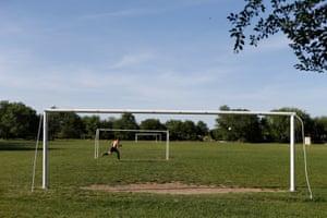 A man runs near goalposts on a football pitch in a settlement in Stavropol region