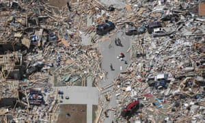 Rescue workers and volunteers stand amid debris of homes one day after they were destroyed by tornado in Vilonia, Arkansas