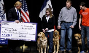 Donald Trump presents a mock check representing $100,000 to members of the Puppy Jake Foundation in Davenport, Iowa, on 30 January 2016.