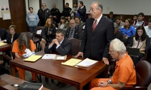 Deborah Leonard and Bruce Leonard sit next to their attorneys in court.