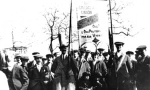 Anne Gambrell's grandfather, right, and great-grandfather, left, holding the TGWU banner at a rally in the 1930s. Two of her aunts are beneath the banner, in matching outfits made by Anne's grandmother.