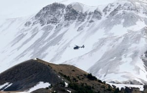 A rescue helicopter from the French Gendarmerie flies over the snow covered French Alps during search operations near the crash site