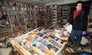 Catherine Hetherington, proprietor of the New Bookshop in Cockermouth, studies the damage done by floodwater.