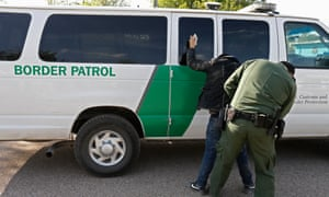 A border patrol agent searches a person suspected of crossing the Rio Grande River to enter the United States illegally near Rio Grande City, Texas on 1 March 2017.