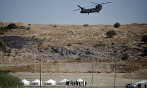 A Greek air force helicopter hovers over a military area on Lesbos as officials prepare a tented area for refugees after a series of fires in the island's Moria camp.