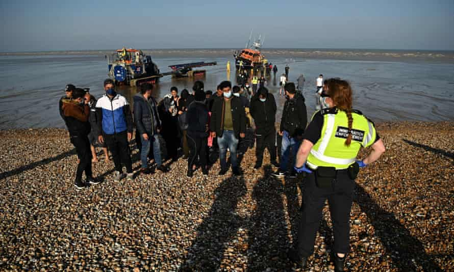 Migrants are escorted to be processed after being picked up by an RNLI lifeboat while crossing the Channel at a beach in Dungeness, Kent