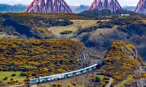 A Caledonian Sleeper train passes the Forth Bridge in eastern Scotland