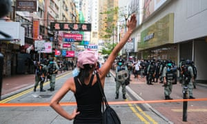 A girl holds up her hand and confront with the police during a banned protest in Hong Kong
