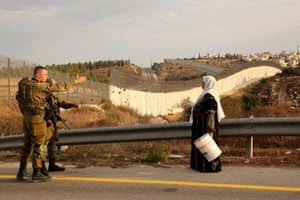 A Palestinian woman waits to cross an Israeli army checkpoint
