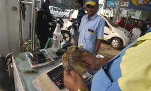 An Indian customer pays for fuel with old 500 rupee notes at a petrol station in New Delhi