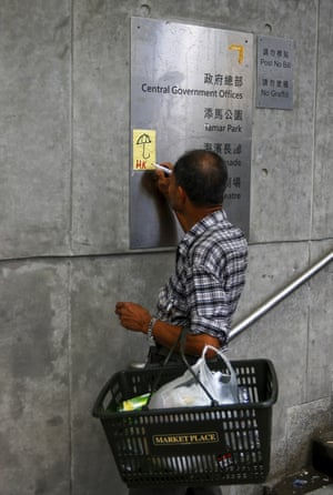 A man writes on a paper note on the wall by the Central Government Office building.