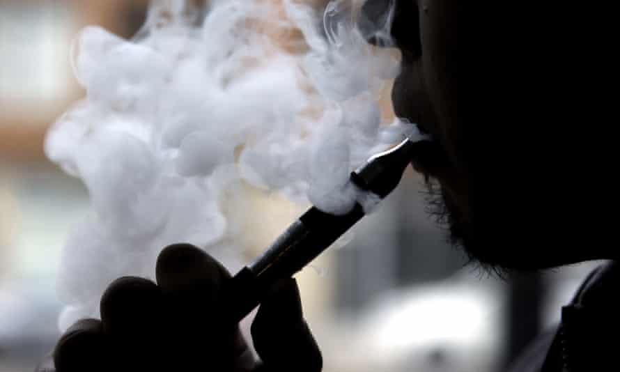 A man smokes an electronic cigarette