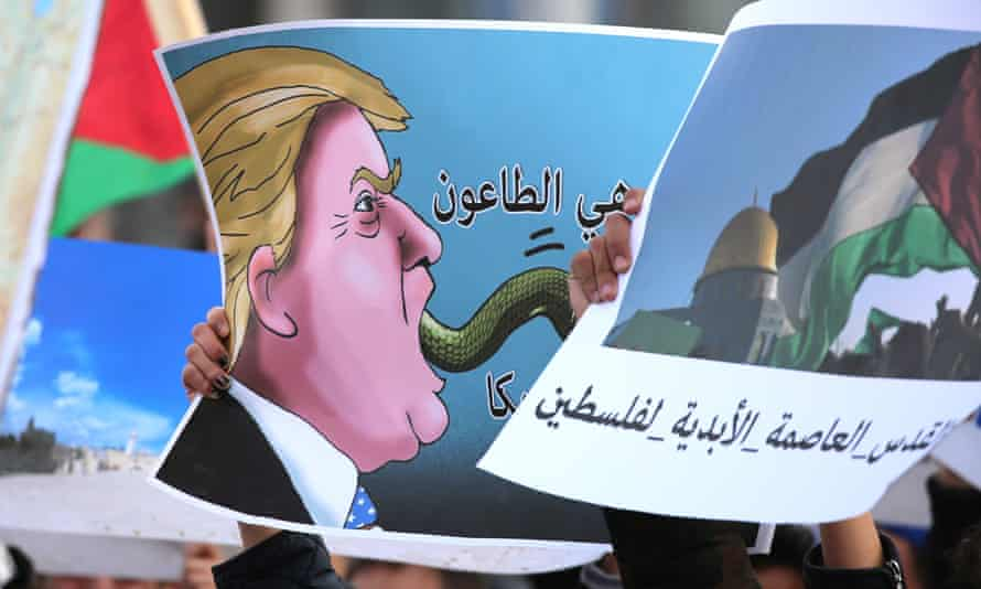 A Jordanian protester holds a poster depicting the US president Donald Trump during a demonstration outside the US embassy in Amman.