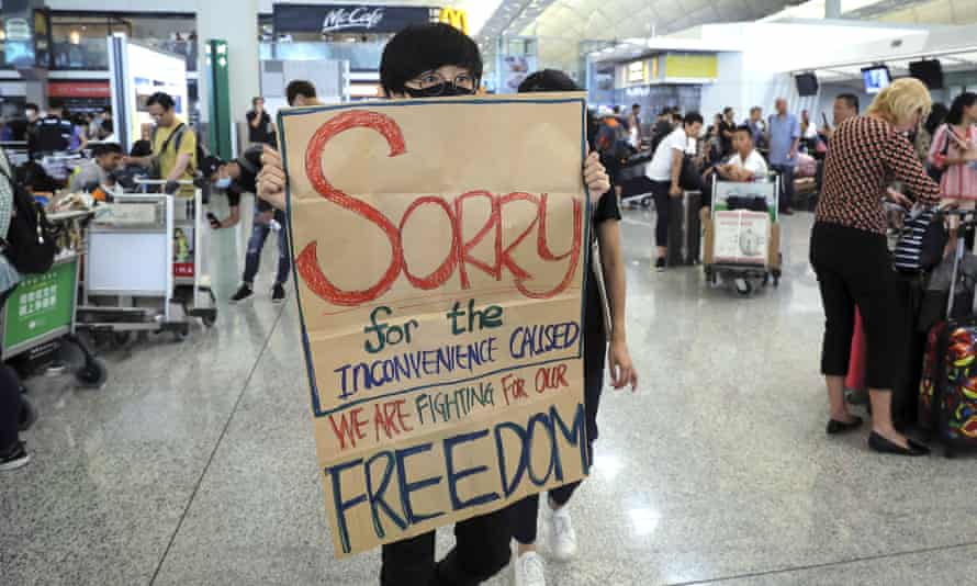 A protester shows a placard to stranded travellers during a demonstration at Hong Kong airport