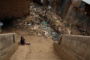 A young baby sits alone at the bottom of some stairs surrounded by litter in Kibera, Nairobi.