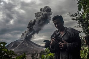A man picks up his dog as he prepares to leave after the danger zone around the volcano is widened