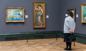 On 4 July 2020; a woman wearing a face mask looks at paintings during preparations for the reopening of the National Gallery.