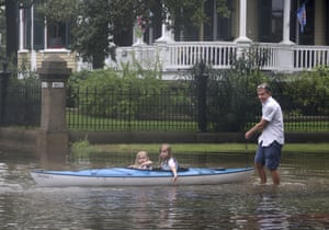 Don Dressler pulls his granddaughters Elsie and Jillian Deans on a kayak through the water on Avenue L after the rain from Tropical Storm Imelda stopped in Galveston, Texas on Wednesday.