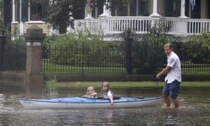 Don Dressler pulls his granddaughters Elsie and Jillian Deans on a kayak through floodwaters from Tropical Storm Imelda in Galveston, Texas.