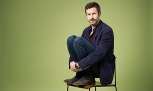Chris O'Dowd crouched on a hardback chair, hugging his knees