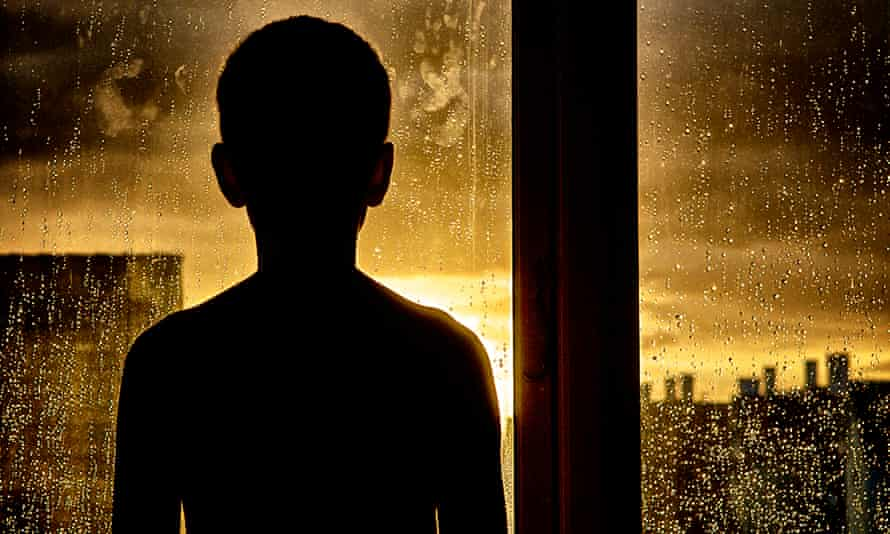 A boy looking out of the window after an intense rain shower at sunset.