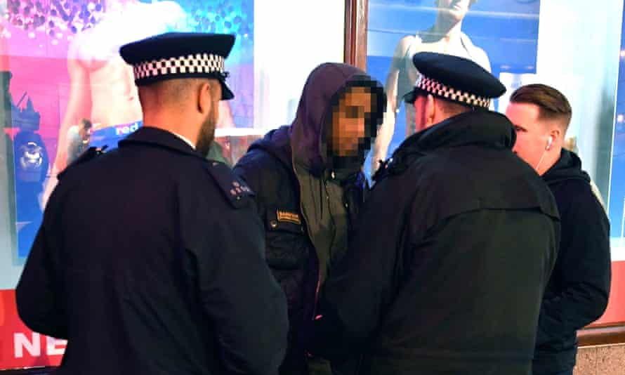 Police officers stop and search a man