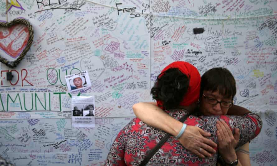 Two women embrace in front of a messages left on a wall of condolence following the blaze at Grenfell Tower.