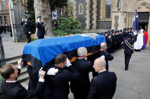 Pallbearers carry the officer's coffin into Southwark Cathedral