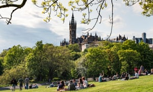 Young people relax in Kelvingrove Park with Glasgow University in the background