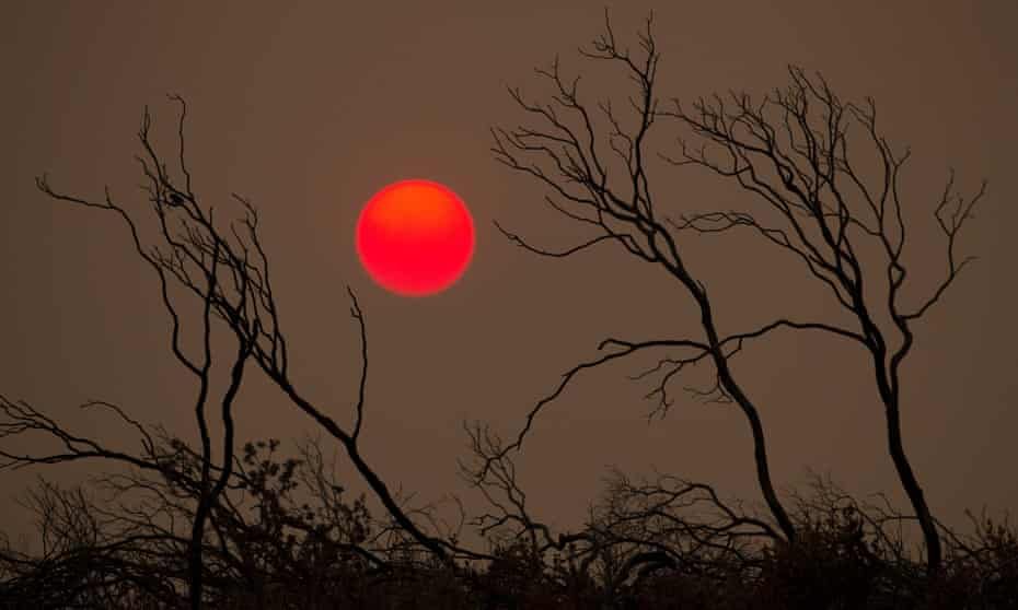 The suns sets over hills burned by the Carr fire, west of Redding.