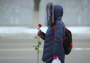 A woman holds a rose while waiting for a bus, Chisinau, Moldova