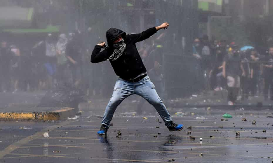 A demonstrator clashes with riot police during protests in Santiago, Chile