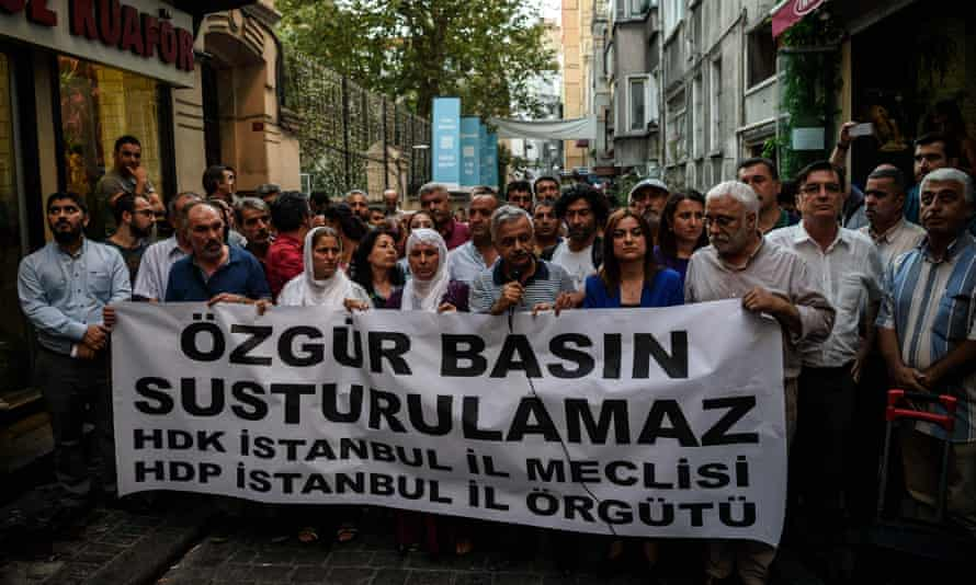 """Protesters in Istanbul hold a banner reading """"Free media cannot be silenced"""" following the closure of Özgür Gündem."""