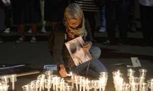 An woman lights candles during a vigil outside the presidential palace in Jakarta.