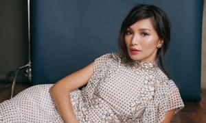Gemma Chan lying in a silver dress