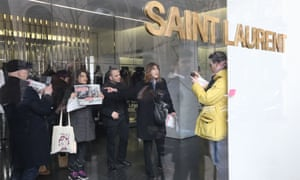 "People hold posters saying ""sexist"" in an Yves Saint-Laurent shop in Paris on Tuesday."