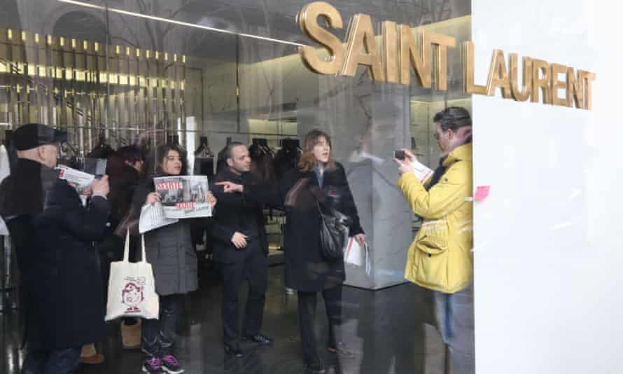 """People hold posters saying """"sexist"""" in an Yves Saint-Laurent shop in Paris on Tuesday."""