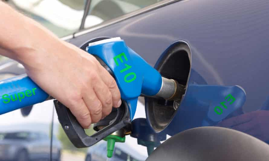 A motorist at the pumps fills up their car with E10