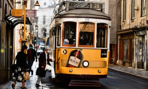 People wearing protective masks board a tram in the area of Baixa District, Lisbon.