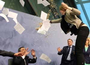 """ALTERNATIVE CROP A woman disrupts a press conference by Mario Draghi (C), President of the European Central Bank, (ECB) following a meeting of the Governing Council ain Frankfurt / Main, Germany, on April 15, 2015. The woman who charged at Draghi calling for an """"end to the ECB dictatorship"""" was quickly escorted out of the premises by security officers before the news conference resumed. AFP PHOTO / DANIEL ROLANDDANIEL ROLAND/AFP/Getty Images"""