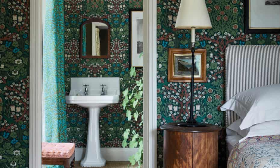 A bedroom with green patterned wallpaper, and a full-length mirror reflecting it