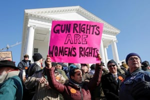 An activist holds up a sign supporting gun rights for women