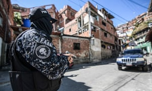 A member of the Bolivarian National Police Special Forces (FAES in Spanish) seen taking position during a Police raid operation against criminal groups at Petare slum in Caracas.