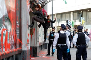 London, UKPolice officers watch as activists climb down from the awning over the Brazilian Embassy's entrance during an Extinction Rebellion climate change protest.