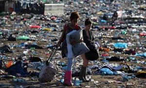 Festivalgoers leave the Glastonbury site through mounds of rubbish.