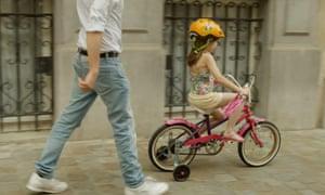 A man walking behind a child riding her bike