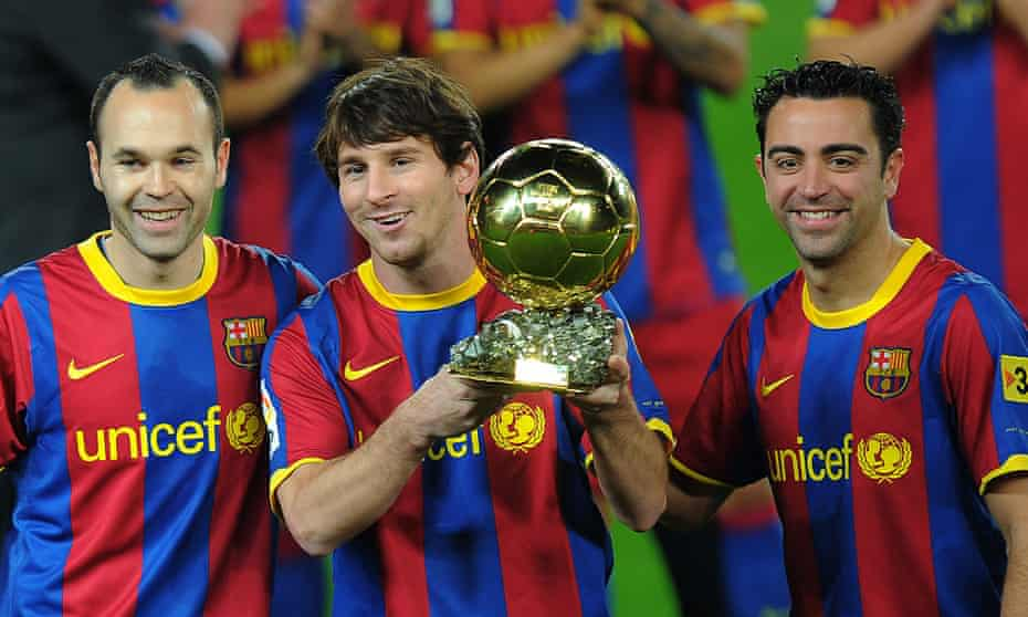 Lionel Messi with the Ballon d'Or in 2011, flanked by Barcelona teammates Xavi (right) and Andrés Iniesta.