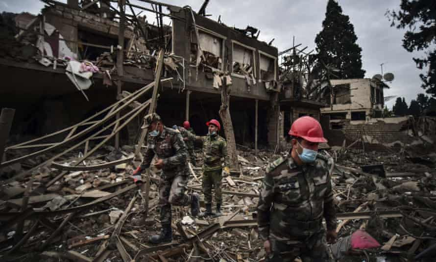 Azerbaijani soldiers and firefighters search for survivors after rocket fire overnight by Armenian forces in a residential area in Ganja, Azerbaijan's second-largest city