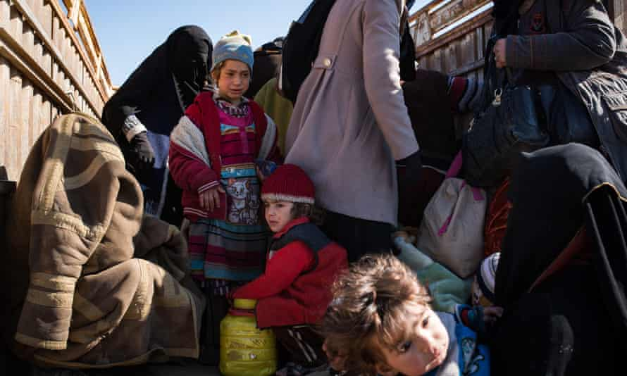 Women and children from suspected Isis families in the back of a truck